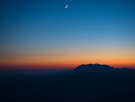 Photo for Panoramic view of sunset and night sky with new moon at mountains silhouette background - Royalty Free Image