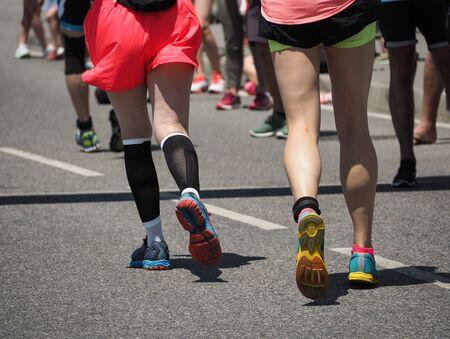 Foto de Group of young running women in jogging shoes on asphalt sport track - Imagen libre de derechos