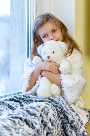 Cute little girl hugging a teddy bear. A cute baby in the room sits at the window in the winter