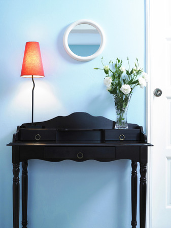 Lamp and vase of flowers on a wooden drawer