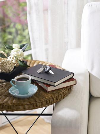 Car keys, tea cup and books on a table.