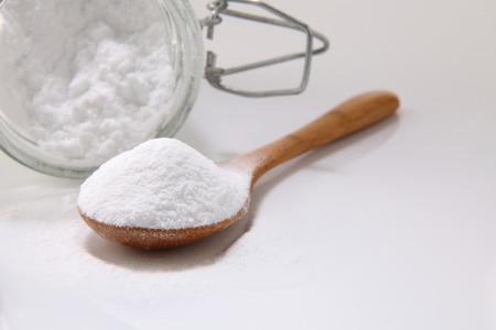 Photo pour wooden spoon full of baking soda on the white background - image libre de droit