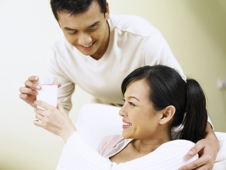 man bring pregnant wife a glass of milk