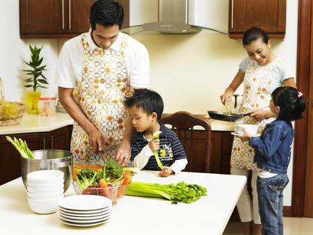 Foto de Family preparing food in the kitchen - Imagen libre de derechos