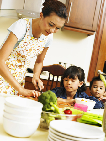 Mother and children preparing meal in the kitchen