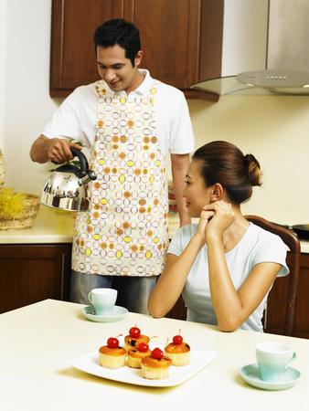 Photo pour couple having tea break in the kitchen - image libre de droit
