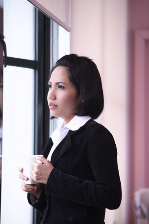 Foto de businesswoman with a mug, looking out of a window - Imagen libre de derechos
