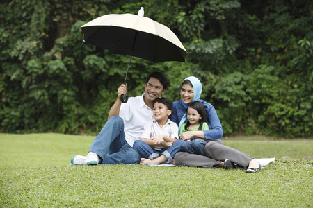 Foto de man holding umbrella for his family - Imagen libre de derechos