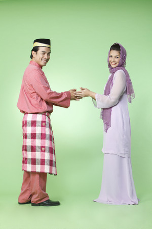 Photo for couple with traditional outfit greeting each other - Royalty Free Image
