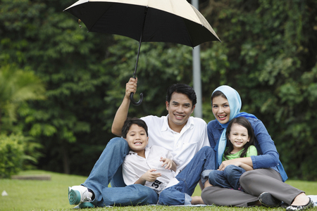 Photo for man holding umbrella for his family - Royalty Free Image