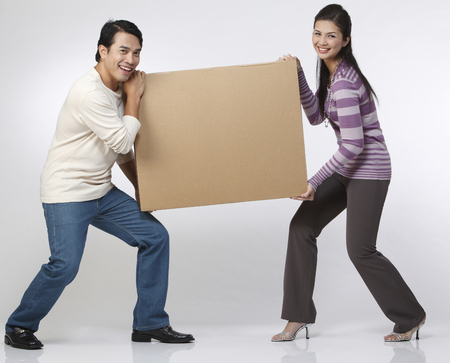 Photo for couple carrying a heavy box - Royalty Free Image