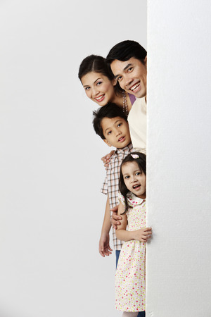 Photo pour familiy hiding behind a huge board - image libre de droit