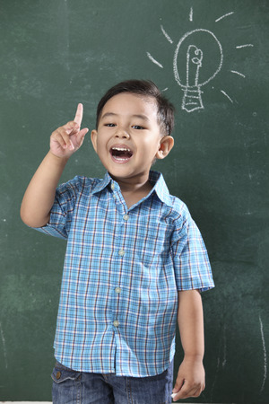 Photo pour malay boy standing in front of the blackboard with light bulb drawing - image libre de droit