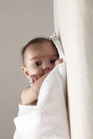 Foto de baby peeping from white towel - Imagen libre de derechos