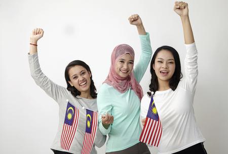 Foto de three multi racial malaysian holding flag wtih raised arm - Imagen libre de derechos