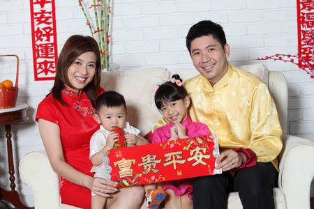 Foto de chinese family sitting on the sofa with chinese new year decoration - Imagen libre de derechos