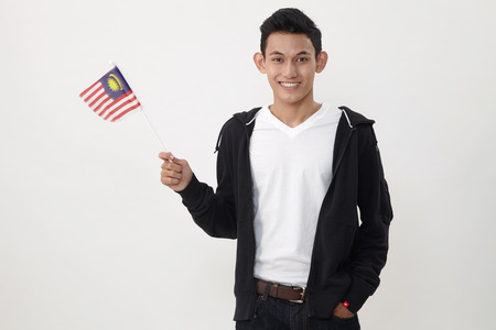 Photo pour malay teenage holding a small malaysiasia flag - image libre de droit