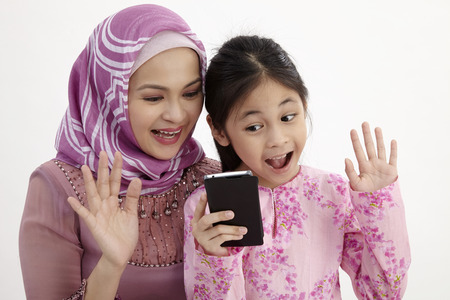 Photo pour Closeup of excited girl and mother making video call with smart phone - image libre de droit