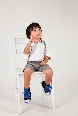 Photo pour chinese boy sitting on the big stool - image libre de droit