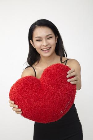 Photo pour Asian woman holding a red heart-shaped pillow. - image libre de droit