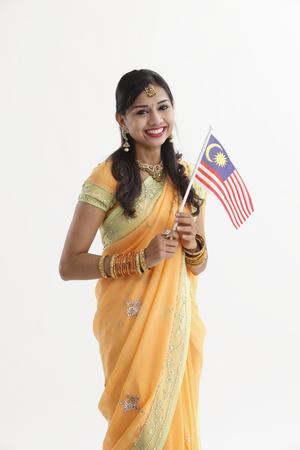 Photo pour Indian woman in glamorous traditional clothing holding malaysia flag celebration merdeka - image libre de droit
