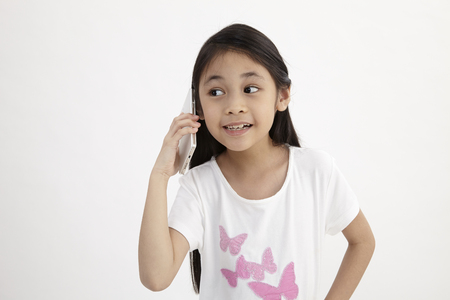 Foto de Childhood and technology. Cute little girl using smart phone. Isolated on white. - Imagen libre de derechos