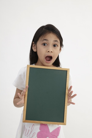 Foto de Cute little girl holding a chalkboard, isolated on white - Imagen libre de derechos