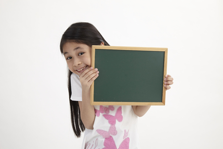 Photo pour Cute little girl holding a chalkboard, isolated on white - image libre de droit