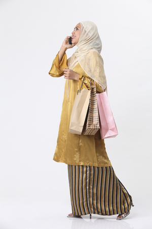 Photo pour Malay woman talking on the phone while holding some shopping bags. - image libre de droit