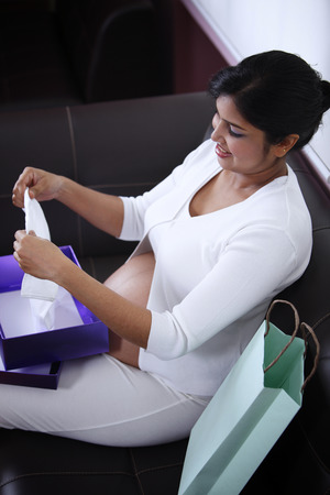 Pregnant mother opening gifts of baby clothes