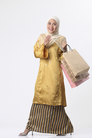 Malay woman holding shopping bags.
