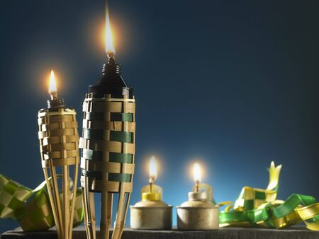 Photo for bamboo torch  oil lamp and ribbon ketupat on the blue background - Royalty Free Image