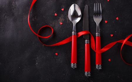 Foto de Romantic Valentine's Day celebration, a set of silverware on a dark background,decorated with red ribbon and hearts.selective focus - Imagen libre de derechos