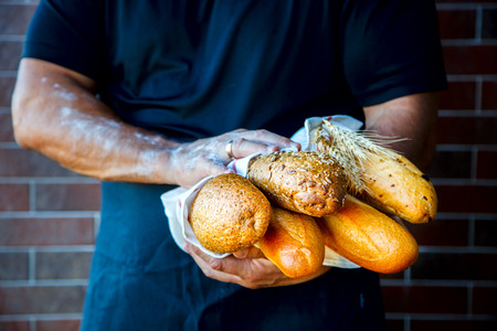 Man Wearing Apron Holding Freshly Baked Loaf Of Bread.selective focus