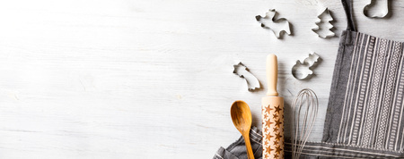 Photo pour Kitchen apron on Holiday Background Concept of Christmas and New Year. Festive preparations. Poster design, rolling and whisk, a wooden spoon and cookie cutters and gingerbread. Copy space for Text. - image libre de droit