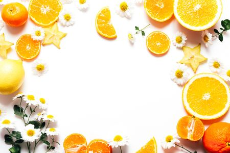 Photo for Frame of sliced oranges and tangerines with flowers on white background, copy space - Royalty Free Image