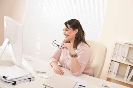 Smiling young businesswoman sitting at office watching computer screen