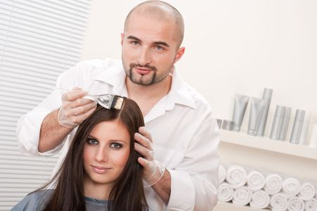 Professional male hairdresser color female customer at design salon
