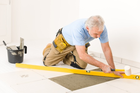 Home improvement, renovation - handyman laying ceramic tile with level