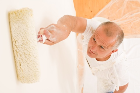 Home decorating mature man painting white wall with paint roller