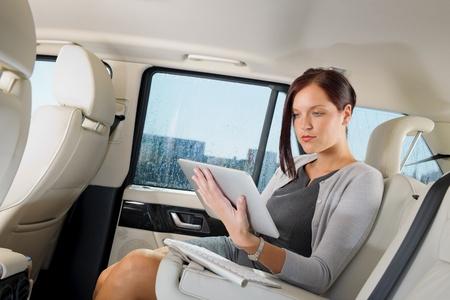 Photo pour Attractive executive female manager work luxury car touch tablet computer - image libre de droit