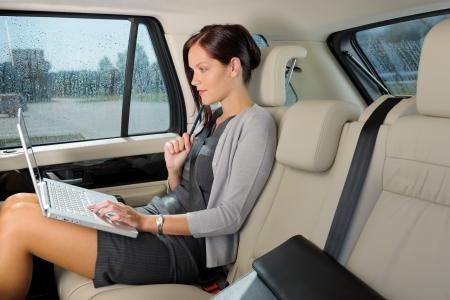 Photo pour Executive woman manager working on laptop sitting car leather backseat - image libre de droit