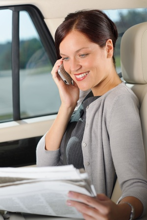 Attractive executive businesswoman sitting in car calling phone checking newspapers