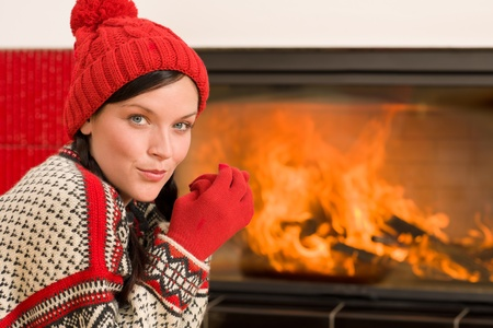 Happy woman warming up by home fireplace wear christmas sweater