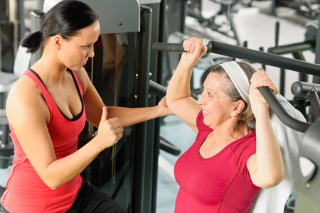 Personal trainer assist senior woman exercising on machine at gym