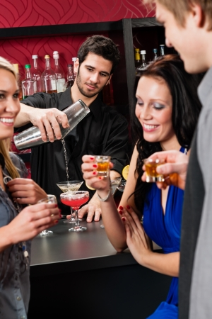Barman making cocktail for young friends at the bar