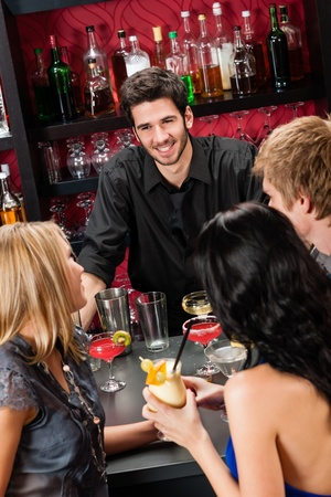 Cheerful barman chatting with young friends at cocktail bar