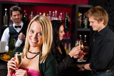 Attractive woman toast champagne with friends at cocktail bar