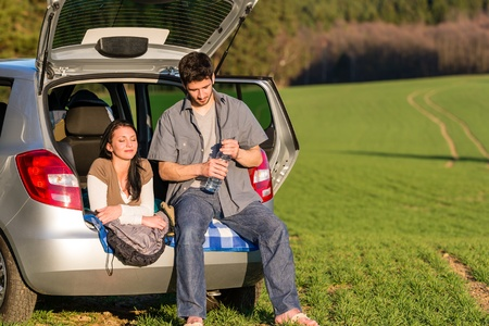 Happy camping couple lying inside car summer sunset countryside