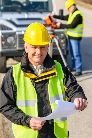Male geodesist in reflective vest and helmet hold land plans